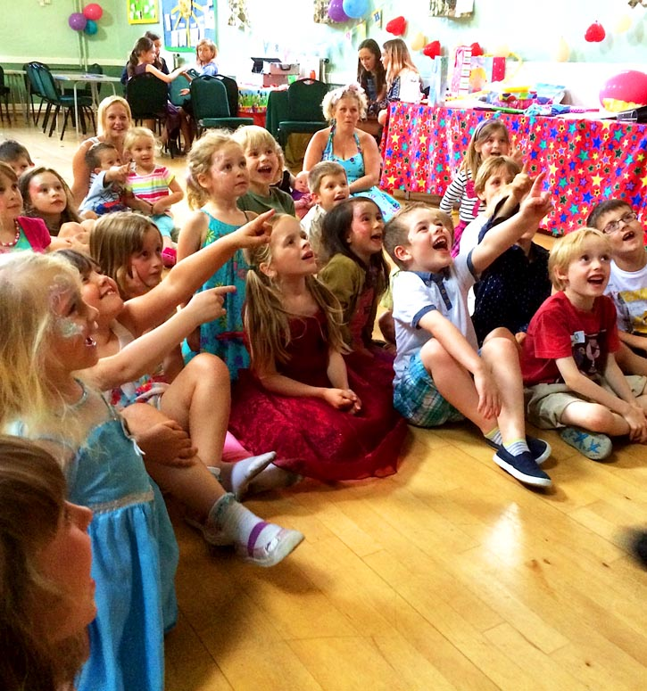 An audience of delighted children watching a children's show at a party