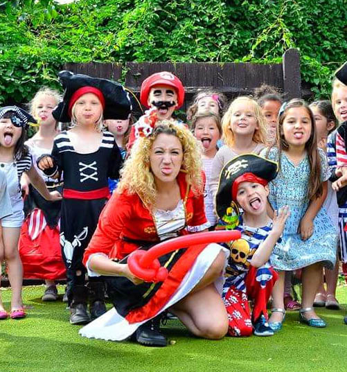 Happy children all costumed as pirates with a female entertainer also costumed as a pirate who is sticking out her tongue